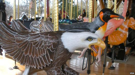 The carousel at the Zoological Park that is populated by exotic and endangered species where a yellow jacket is one of the animals for riding.