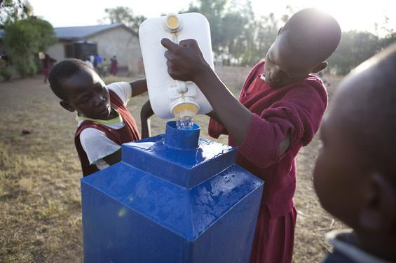 Thirteen-year-old  Susan Awino (left) pours water with another student from the well into a  container for handwashing. Students  at Ogwodo Primary School in Sidho, Kenya, fill containers each morning  for handwashing and drinking water. CARE assists governments and other  partners in Kenya, Zambia and Mali with water and sanitation in schools  to give girls like Susan a better chance at  finishing their education.