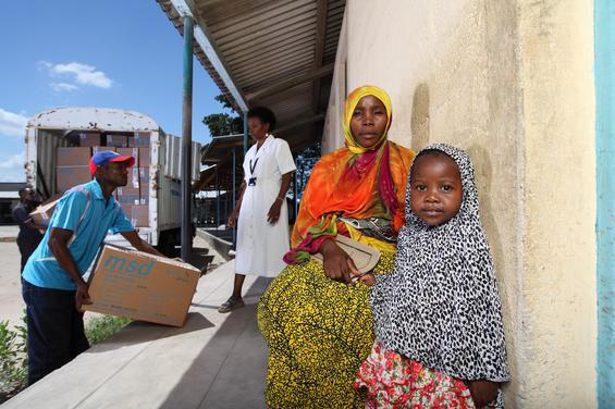 Mother and child await medical care outside a clinic in Tanzania.